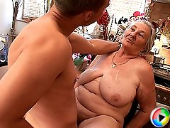 A fat older granny works on two younger cocks